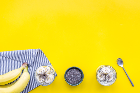 Idea for healthy breakfast. Banana pudding with chia seeds on yellow table with blue tablecloth top view.
