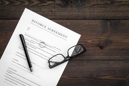 Divorce agreement. Wedding ring on document on dark wooden background top view.