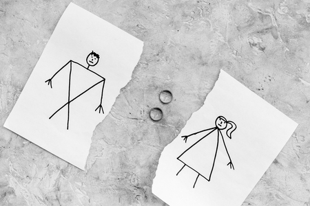 Divorce or falling apart concept. Torn sheet of paper with drawn man and woman, wedding rings between parts on grey background top view.