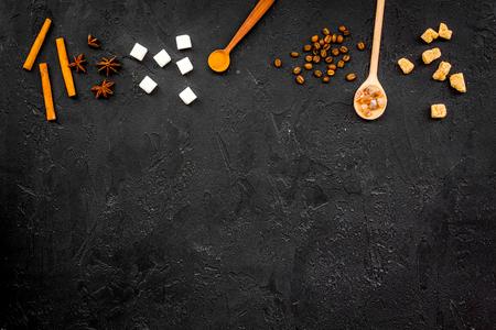 Ingredients for sweet bakery. Cinnamon, sugar, badian on black table top view.