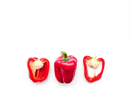 Layout of red sweet bell pepper slices on white background top view.