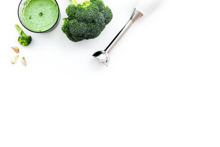 Cook green cream soup with vegetables. Broccoli and blender on white table top view copy space