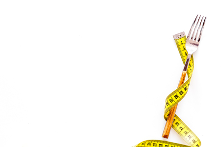Diet, weight loss, slimming concept. Fork with wound measuring tape on white background top view.
