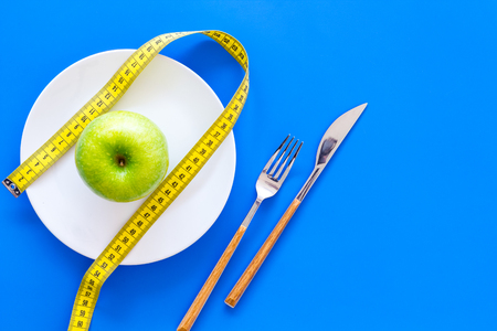 Proper nutrition with dietary fibre for weight loss. Apple on plate near measuring tape on blue background top view. Stock Photo