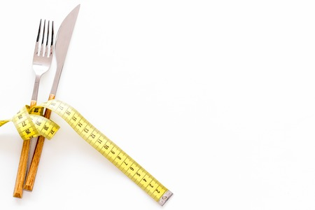 Diet, weight loss, slimming concept. Fork and knife with wound measuring tape on white background top view space for text Stock Photo