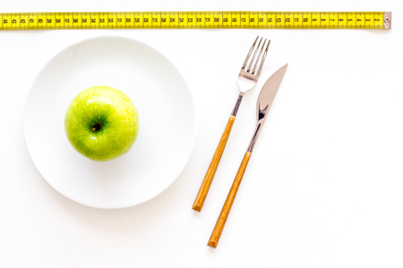 Proper nutrition with dietary fibre for weight loss. Apple on plate near measuring tape on white background top view copy space Stock Photo