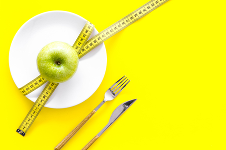 Proper nutrition with dietary fibre for weight loss. Apple on plate near measuring tape on yellow background top view copy space