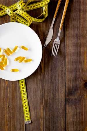 Pills or dietary supplement for weight loss. Treatment of obesity. Treatment of anorexia. Gold pills on plate near measuring tape on dark wooden background top view copy space