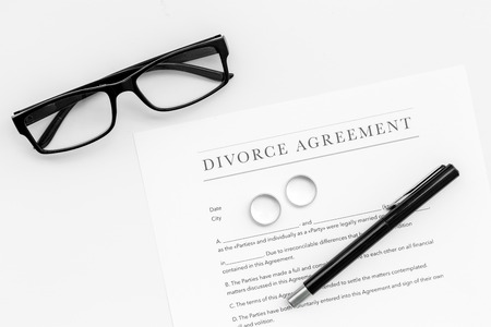 Divorce agreement. Wedding ring on document on white background top view. Stock Photo