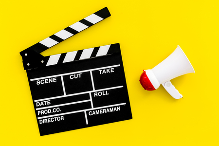 Film director, producer concept. Electronic megaphone and clapperboard on yellow background top view.