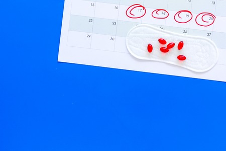 Menstruation cycle concept. Menstruation calendar with sanitary pads, contraceptive pills on blue background top view.