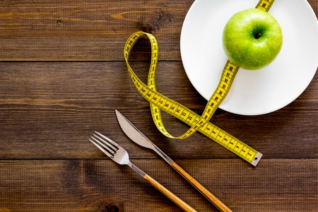 Proper nutrition with dietary fibre for weight loss. Apple on plate near measuring tape on dark wooden background top view.