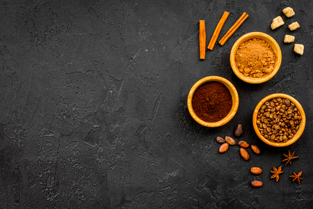 Flavoring products for making desserts. Cinnamon, cocoa, coffee on black table top view space for text