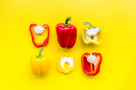 Layout of red and yellow sweet bell pepper slices on yellow background top view pattern