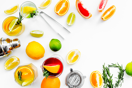 Bartender workplace for make fruit cocktail with alcohol. Shaker, strainer and other bar tools near citrus fruits and glass with cocktail on white background top view copy space Stock Photo