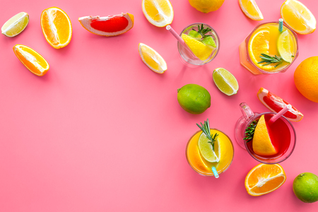 Tropical fruit cocktail with alcohol. Glass with beverage near oranges, grapefruit, lime and rosemary on pink background top view copy space Stok Fotoğraf