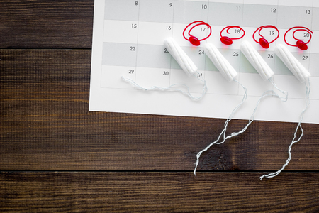 Menstrual period concept. Menstruation calendar with hygienic tampons and pills on dark wooden background top view space for text Фото со стока