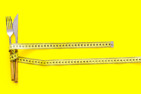 Diet, weight loss, slimming concept. Fork and knife with wound measuring tape on yellow background top view space for text