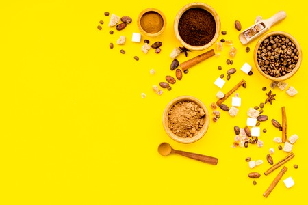 Ingredients for bakery and desserts. Cinnamon, cocoa, coffee, sugar, spices on yellow background top view space for text Stock Photo