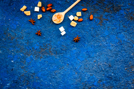 Seasoning for sweets and desserts. Sugar, badian, cinnamon on blue table top view copy space Stock Photo