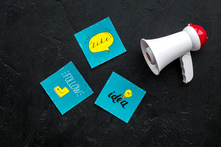 Social media announcements concept. Megaphone near social media icons on black background top view Stock Photo