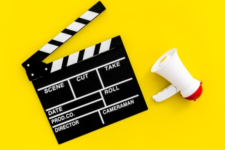 Film director, producer concept. Filming. Electronic megaphone and clapperboard on yellow background top view Stockfoto