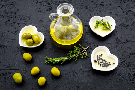Fresh olive oil in glass jar near green olives and branch of rosemary on black background top view