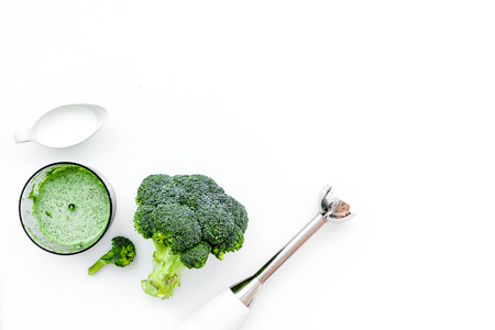 Cook green cream soup with vegetables. Broccoli, cream, spices, blender on white table top view copy space Standard-Bild