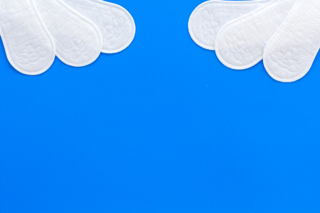 Woman hygiene products. Critical days concept. Sanitary pads on blue background top view copy space Stock Photo