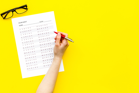 Take the exam, write the exam. Hand with pen near exam paper on yellow background top view copy space Stock Photo