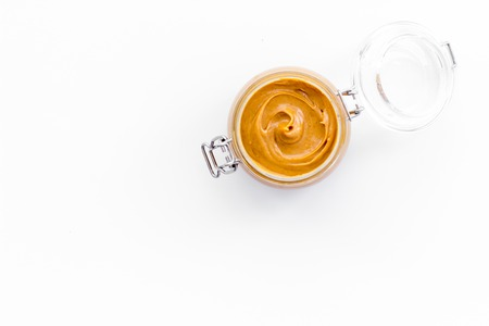 Nut butter, peanut butter in glass jar on white background top view copy space