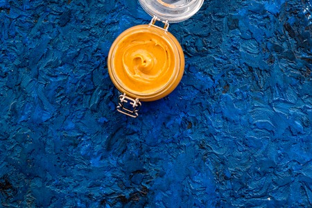 Nut butter in glass jar on blue background top view copy space Stock Photo