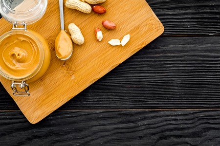 Make peanut butter. Paste in glass jar on cutting desk near peanut on black wooden background top view copy space
