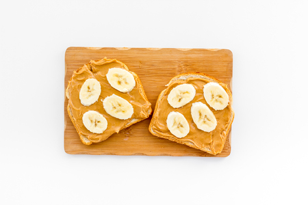 Sandwich with nut butter and banana for breakfast on white background top view Stock Photo