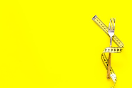 Proper nutrition for slimming. Fork with wound measuring tape on yellow background top view copy space Stock Photo