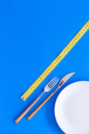 Diet for weight loss concept. Proper nutrition. Medical starvation. Empty plate with fork and knife near measuring tape on blue background top view mockup Фото со стока