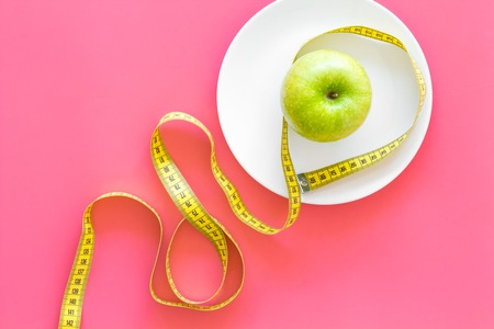 Proper nutrition with dietary fibre for weight loss. Apple on plate near measuring tape on pink background top view copy space