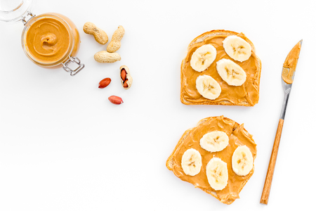 Sandwich with nut butter and banana for breakfast on white background top view copy space
