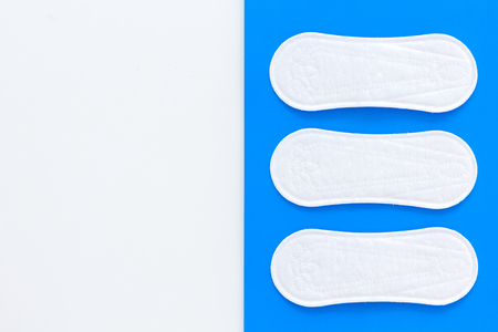 Woman hygiene products. Critical days concept. Sanitary pads on blue background top view copy space pattern Stock Photo