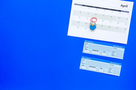 Plan a trip. Buy airplane tickets. Tickets near calendar with date circled on blue background top view copy space