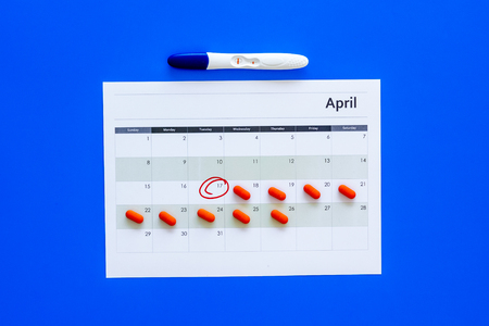 Planning pregnancy. Positive pregnancy test near calendar page and pills on dark wooden background top view.