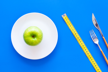 Proper nutrition with dietary fibre for weight loss. Apple on plate near measuring tape on blue background top view Stock Photo