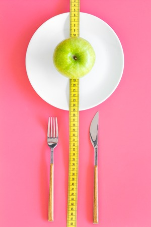 Proper nutrition with dietary fibre for weight loss. Apple on plate near measuring tape on pink background top view Stock Photo