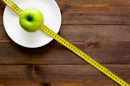 Proper nutrition with dietary fibre for weight loss. Apple on plate near measuring tape on dark wooden background top view copy space