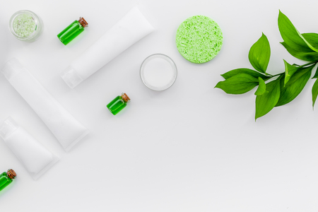 Organic skin care products. Cream, lotion, tonic. oil near green leaves on white background top view pattern