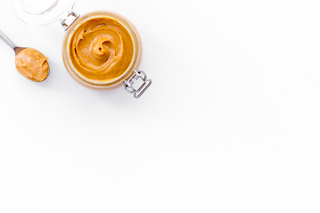 Nut butter, peanut butter in glass jar and spoon with butter on white background top view copy space