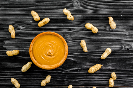 Product for hearty breakfast. High-calorie product. Peanut butter in bowl near nuts in shell on black wooden background top view