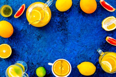 Hot fragrant tea with fruits. Teacup and teapot near citruses on blue background top view copy space