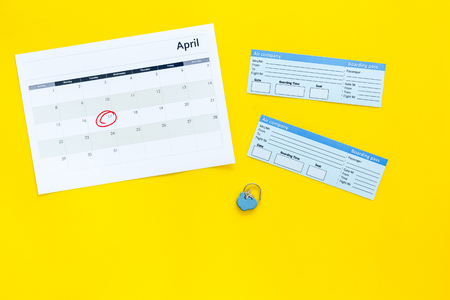 Plan a trip. Buy airplane tickets. Tickets near calendar with date circled on yellow background top view copy space Stock Photo
