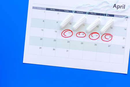 Menstrual period concept. Menstruation calendar with hygienic tampons on blue background top view space for text